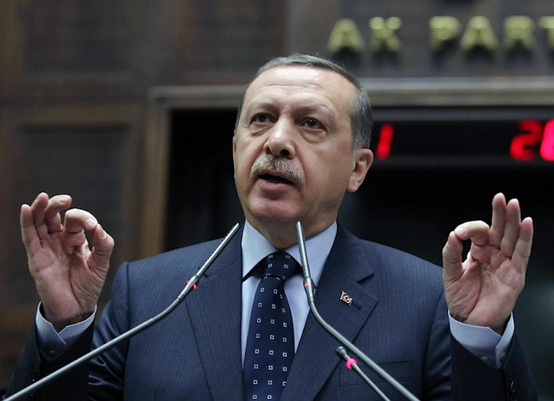 Turkey's Prime Minister Recep Tayyip Erdogan addresses his supporters and lawmakers at the parliament in Ankara, Turkey, Tuesday, May 14, 2013. Erdogan said authorities have detained four more people in connection with two car bomb attacks in a Turkish town near the Syrian border, bringing the number of suspects in custody to 13. Erdogan also said Tuesday the death toll in the attacks has increased to 51.(AP Photo)