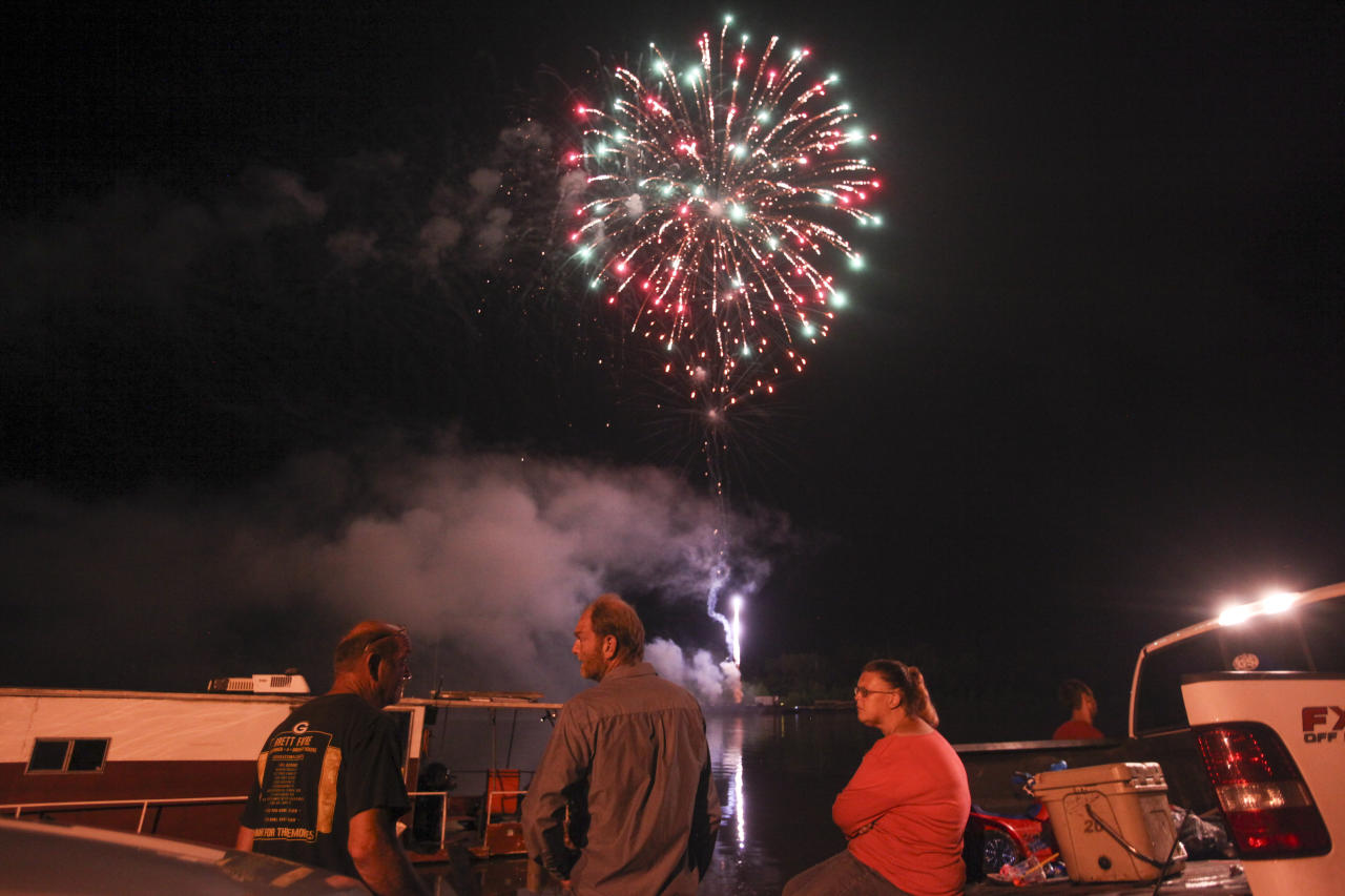 In this Wednesday, July 4, 2018 photograph. Kelly Phillips talks with a couple as fireworks explode over head during the Fourth of July Fireworks Show Vicksburg Riverfront in Vicksburg, Miss. (Courtland Wells/The Vicksburg Post via AP)