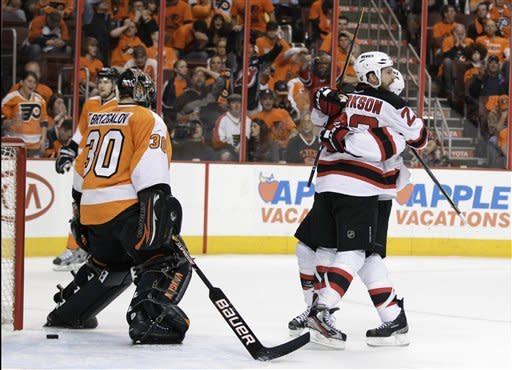 New Jersey Devils' David Clarkson, center, and Zach Parise, right, celebrate after Clarckson's goal against Philadelphia Flyers' Ilya Bryzgalov, of Russia, in the first period of Game 5 of a second-round NHL hockey Stanley Cup playoff series, Tuesday, May 8, 2012, in Philadelphia. New Jersey won 3-1 and took the series 4-1. (AP Photo/Matt Slocum)