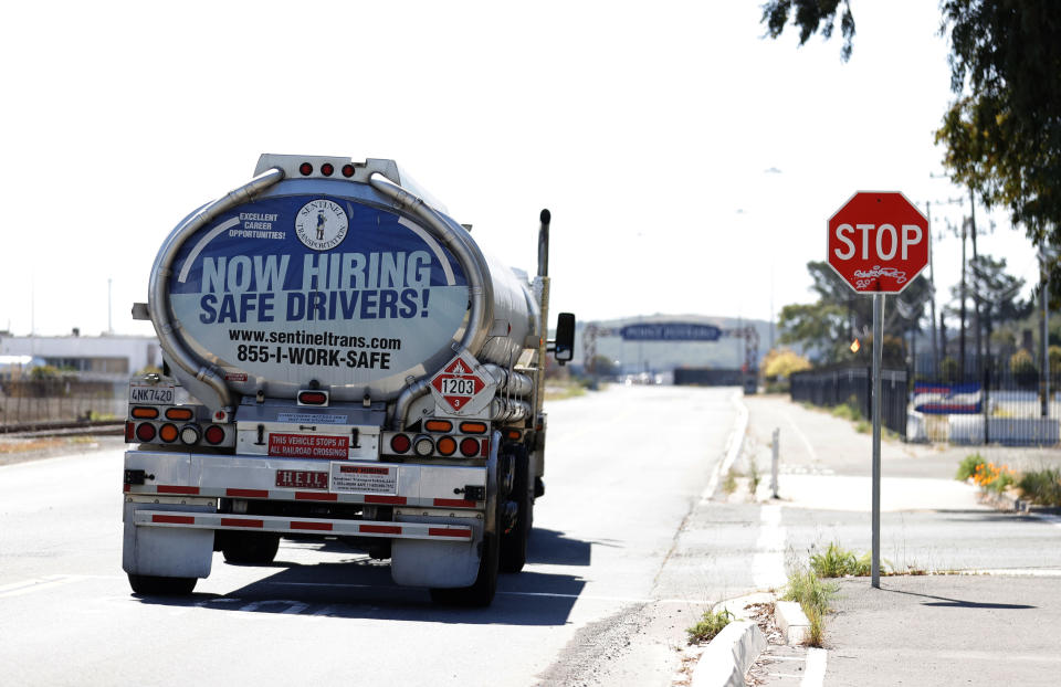 RICHMOND, CALIFORNIA - APRIL 29: A now hiring advertisement appears on the back of a fuel trucks on April 29, 2021 in Richmond, California. A lack of qualified truck drivers could lead to a shortage and gasoline this summer and could cause prices to spike. A gallon of regular unleaded gas is already at or around $4.00 in parts of California. (Photo by Justin Sullivan/Getty Images)