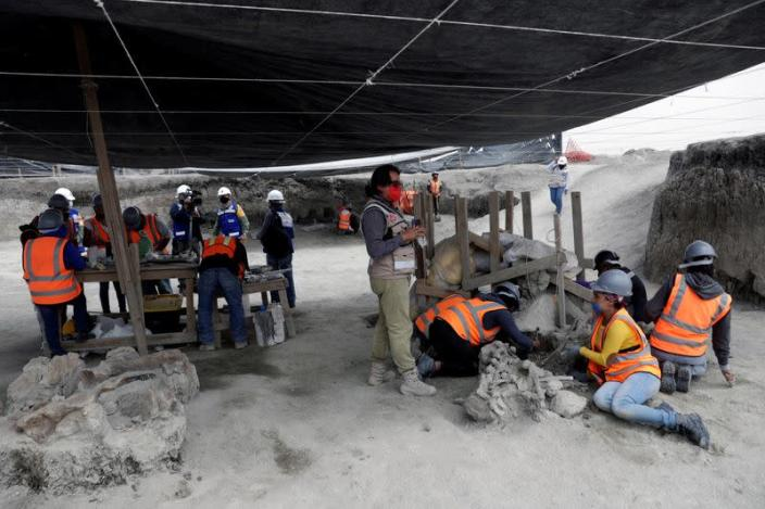 An archaeologist and a worker of Mexico's National Institute of Anthropology and History (INAH) work at a site where more than 100 mammoth skeletons have been identified, along with a mix of other ice age mammals, in Zumpango