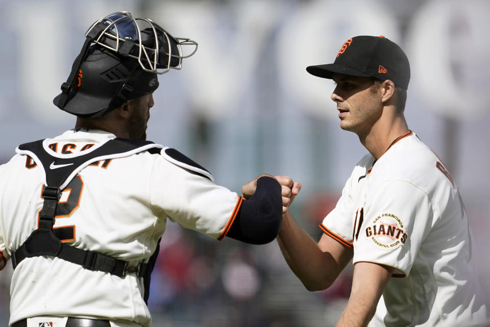 San Francisco Giants catcher Curt Casali, left, celebrates with pitcher Tyler Rogers after the Giants defeated the Miami Marlins in a baseball game in San Francisco, Sunday, April 25, 2021. (AP Photo/Jeff Chiu)