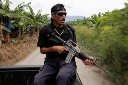 A vigilante rides on the back of a truck while patrolling the municipality of Coahuayana