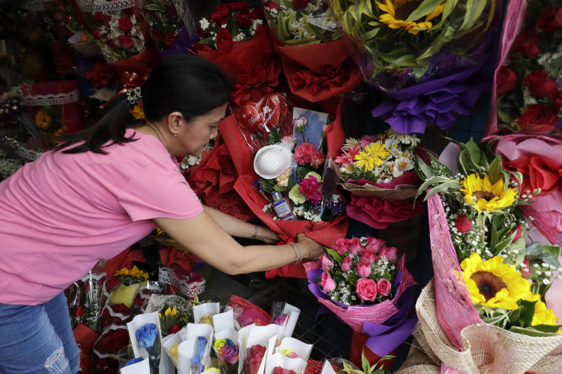 "Shop owner Mary Jane Villegas arranges a Valentines flower arrangement which they called ""anti-nCoV bouquet"" in Alabang, metropolitan Manila, Philippines Thursday, Feb. 13, 2020. Villegas said she placed protective face masks, alcohol, soap, toothpaste and gloves in her bouquet to remind people that flowers are not the only things you can give during Valentines but also protection against the COVID-19. The ""anti-nCoV"" bouquet is sold for P1,300 or U.S. $26. (AP Photo/Aaron Favila)"