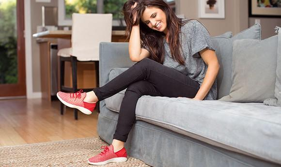 A young woman sitting on a couch wearing a pair of red Skechers shoes.