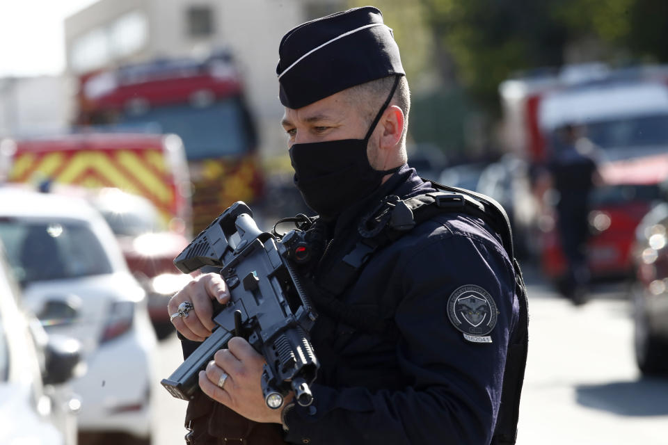 Police officer blocks the access next to the Police station in Rambouillet, south west of Paris, Friday, April 23, 2021. A French police officer was stabbed to death inside her police station Friday near the famed historic Rambouillet chateau, and her attacker was shot and killed by officers at the scene, authorities said. The identity and the motive of the assailant were not immediately clear, a national police spokesperson told The Associated Press. The police officer was a 49-year-old administrative employee in the station, the spokesperson said. (AP Photo/Michel Euler)