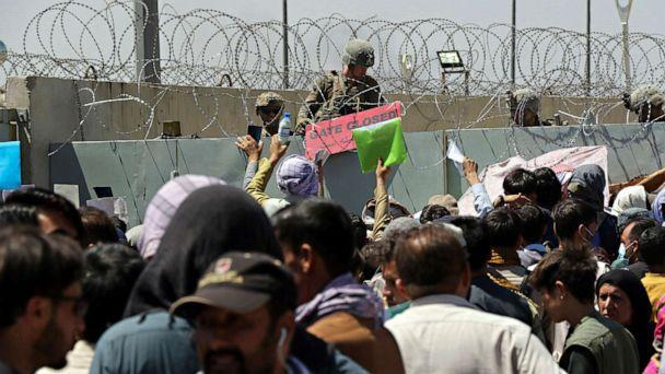 PHOTO: A U.S. soldier holds a sign indicating a gate is closed as hundreds of people gather, some holding documents, near an evacuation control checkpoint on the perimeter of the Hamid Karzai International Airport, in Kabul,  Aug. 26, 2021. (Wali Sabawoon/AP)
