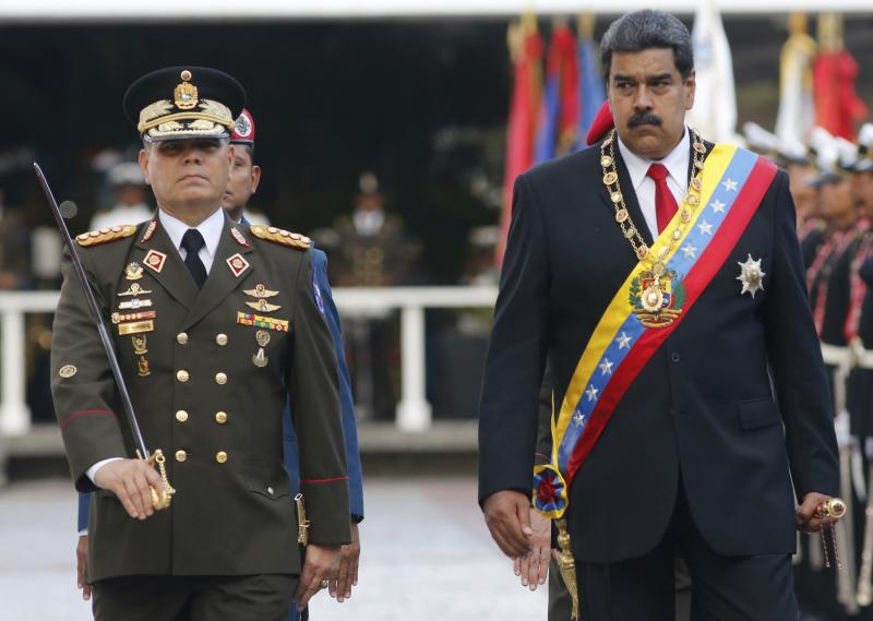 FILE - In this May 24, 2018 file photo, Venezuela's President Nicolas Maduro, right, walks with his Defense Minister Vladimir Padrino Lopez as they review the troops during a military parade at Fort Tiuna in Caracas, Venezuela. On Thursday, March 26, 2020, the U.S. Justice Department made public it has charged in several indictments against Maduro and his inner circle, including Padrino, that the leader has effectively converted Venezuela into a criminal enterprise at the service of drug traffickers and terrorist groups as he and his allies stole billions from the South American country. (AP Photo/Ariana Cubillos, File)