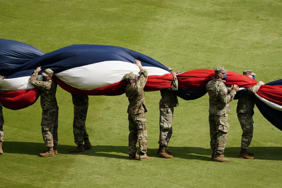 Military members work to gather up a large United States flag stretched across the outfield during a Memorial Day ceremony before a baseball game between the Washington Nationals and the Atlanta Braves, Monday, May 31, 2021, in Atlanta. (AP Photo/John Bazemore)