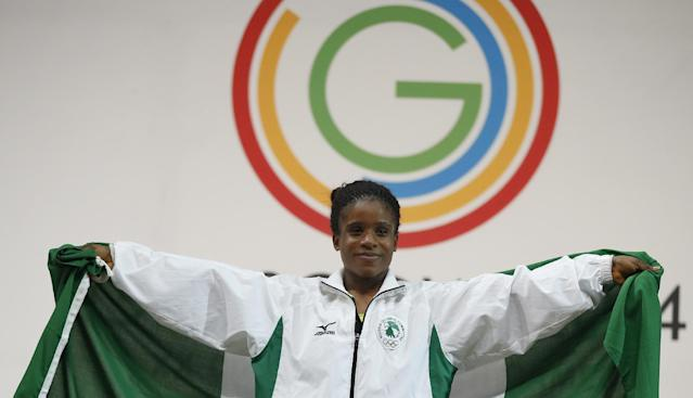 Gold medalist Chika Amalaha of Nigeria, wraps herself in the national flag of Nigeria as she stands on the winners podium during the medal ceremony for the women's 53 kg weightlifting competition at the Commonwealth Games Glasgow 2014, in Glasgow, Scotland, Friday, July, 25, 2014. (AP Photo/Alastair Grant)