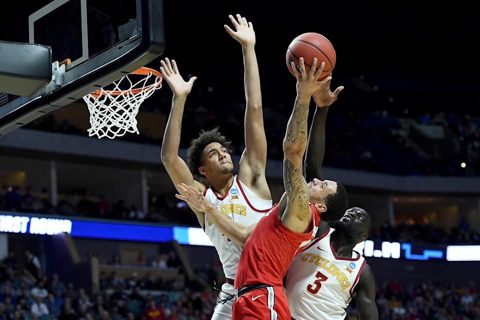 <p>George Conditt IV #4 and Marial Shayok #3 of the Iowa State Cyclones block Duane Washington Jr. #4 of the Ohio State Buckeyes during the first half in the first round game of the 2019 NCAA Men's Basketball Tournament at BOK Center on March 22, 2019 in Tulsa, Oklahoma. (Photo by Stacy Revere/Getty Images) </p>