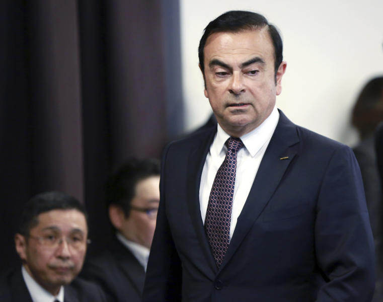 FILE - In this May 12, 2016, file photo, then Nissan Motor Co. President and CEO Carlos Ghosn arrives for a joint press conference with Mitsubishi Motors Corp. in Yokohama, near Tokyo. At left is Nissan Chief Executive Hiroto Saikawa. Japan's court has denied the prosecutor's request to extend detention of ex-Nissan chair Carlos Ghosn. (AP Photo/Eugene Hoshiko, File)