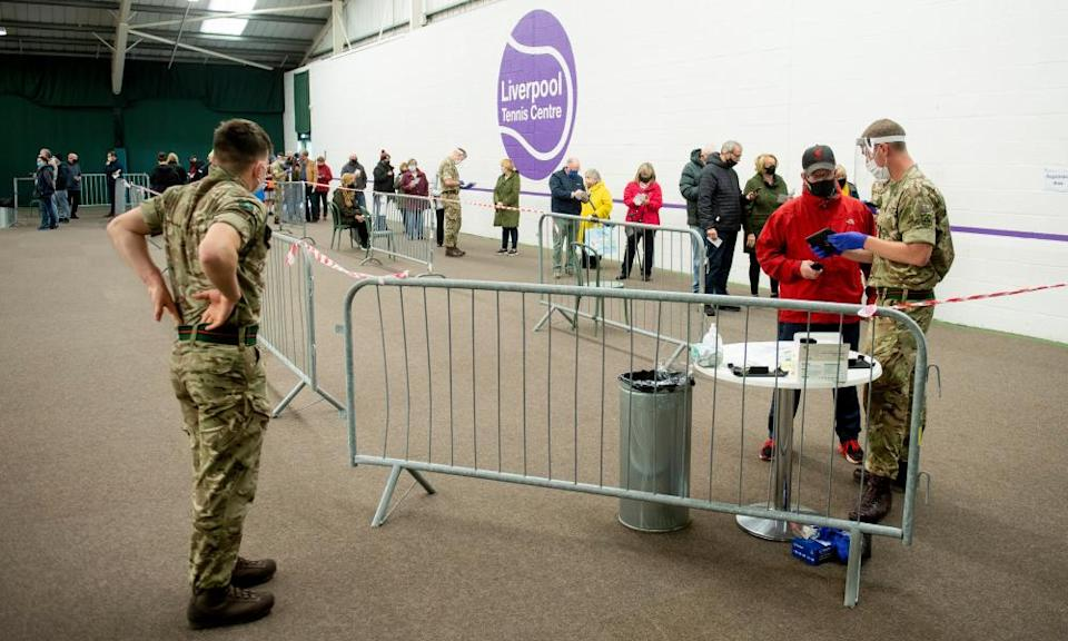 Two uniformed British soldiers deal with a queue of people awaiting Covid-19 testing in Liverpool as part of Operation Moonshot.