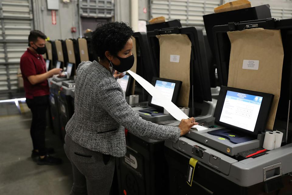 Election worker seen checking voting machines.