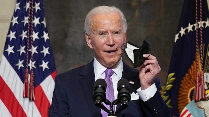 President Biden holds up a face mask as he speaks about the fight to contain the coronavirus pandemic, Jan. 26. (Kevin Lamarque/Reuters)