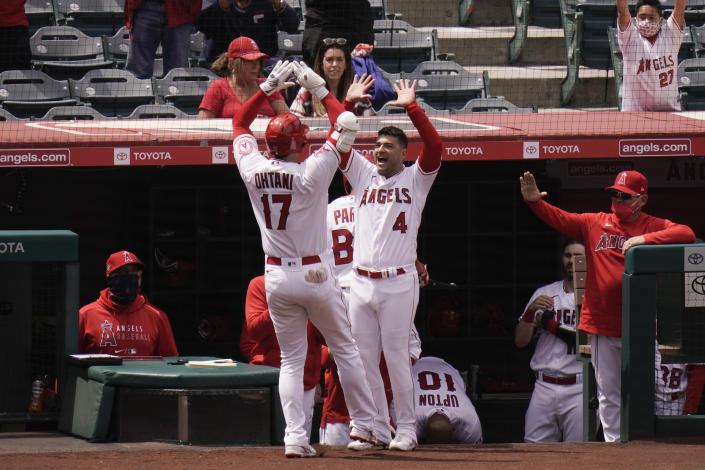 Los Angeles Angels' Shohei Ohtani, left, of Japan, celebrates his home run with Jose Iglesias during the third inning of a baseball game against the Texas Rangers, Wednesday, April 21, 2021, in Anaheim, Calif. (AP Photo/Jae C. Hong)