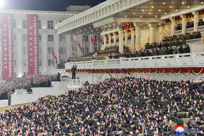 """In this photo provided by the North Korean government, people wave the national flags as North Korean leader Kim Jong Un, center top, attends a military parade, at Kim Il Sung Square in Pyongyang, North Korea Thursday, Jan. 14, 2021. North Korea rolled out developmental ballistic missiles designed to be launched from submarines and other military hardware in a parade that punctuated leader Kim Jong Un's defiant calls to expand his nuclear weapons program. Independent journalists were not given access to cover the event depicted in this image distributed by the North Korean government. The content of this image is as provided and cannot be independently verified. Korean language watermark on image as provided by source reads: """"KCNA"""" which is the abbreviation for Korean Central News Agency. (Korean Central News Agency/Korea News Service via AP)"""