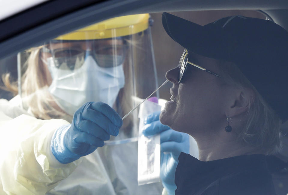 Medical staff take a COVID-19 test from a visitor to a drive through community based assessment centre in Christchurch, New Zealand, Thursday, Aug. 13, 2020. Health authorities in New Zealand are scrambling to trace the source of a new outbreak of the coronavirus as the nation's largest city, Auckland, goes back into lockdown (AP Photo/Mark Baker)
