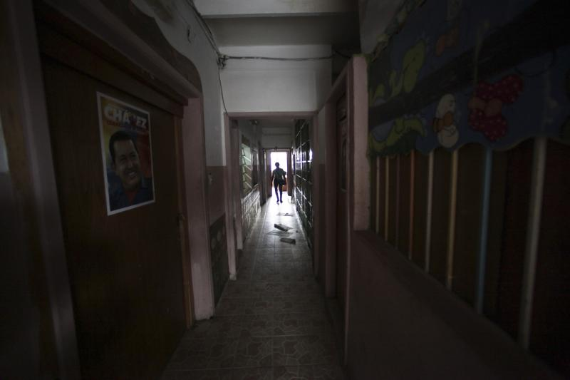 In this Sept. 27, 2012 photo, a woman walks in a hallway inside what was once a school and is now a government provided shelter for families who have lost their homes due to flooding, in Caracas, Venezuela. Fear of every stripe, like the loss of government housing like this one, permeates the intensely polarized election campaign, with many votes to be decided based not on the candidates' promises but rather on what worries people most. Chavez has continuously warning of chaos and the dismantling of the generous welfare state he built if he is voted out of office in the Oct. 7 vote. (AP Photo/Fernando Llano)