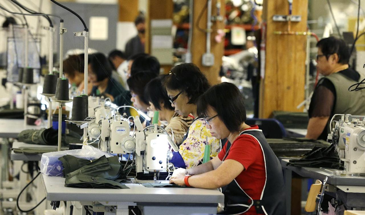 FILE - In this Wednesday, Aug. 31, 2016, file photo, a group of workers at the C.C. Filson Co. manufacturing facility work at their sewing machines, in Seattle. On Monday, Oct. 17, 2016, the Federal Reserve reports on U.S. industrial production for September. (AP Photo/Ted S. Warren, File)