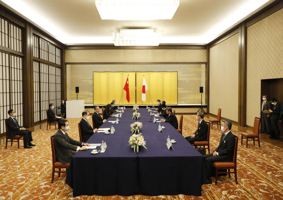China' Foreign Minister Wang Yi, third left, meets with his Japanese counterpart Toshimitsu Motegi, third right, amid the coronavirus outbreak, in Tokyo on Tuesday, Nov. 24, 2020. Wang met Motegi on Tuesday to discuss ways to revive their pandemic-hit economies as well as regional concerns over China's growing influence. (Issei Kato/Pool Photo via AP)