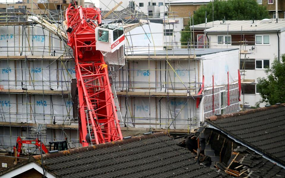 The crane collapsed on a site where flats are being constructed, crashing onto two adjacent houses - Hannah McKay/Reuters