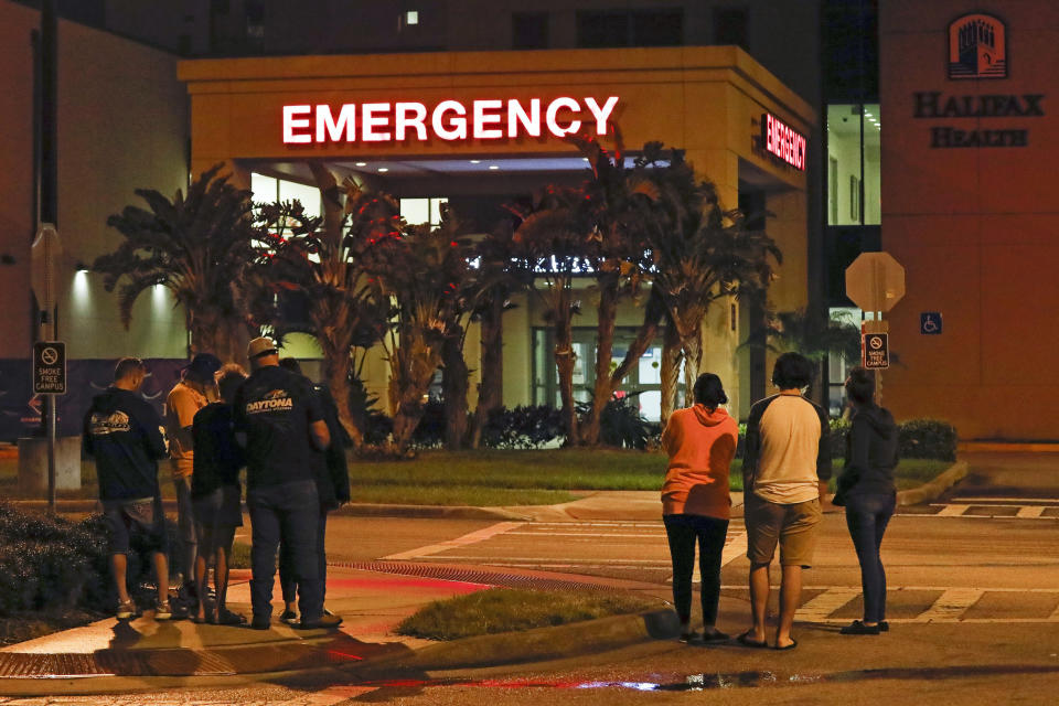 Race fans wait outside the emergency room of Halifax Health Medical Center where Ryan Newman was taken after he was involved in a crash during the final lap of the NASCAR Daytona 500 auto race at Daytona International Speedway, Monday, Feb. 17, 2020, in Daytona Beach, Fla. (AP Photo/Terry Renna)