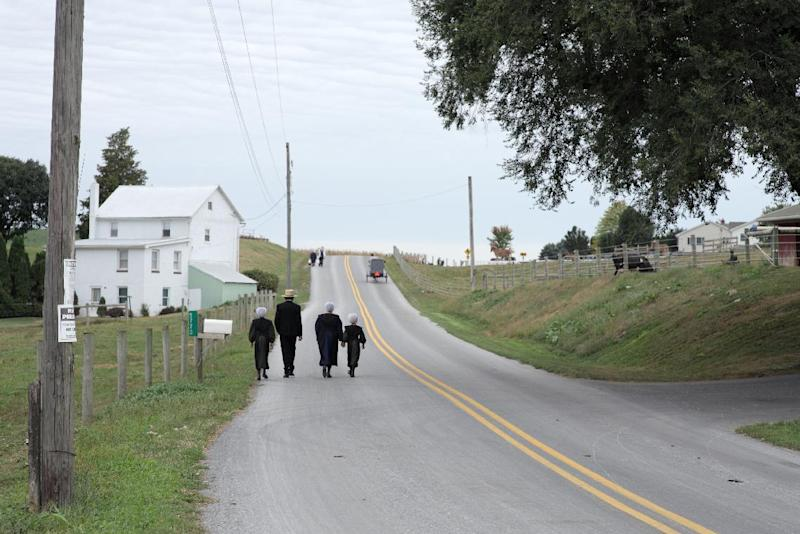 """In this image released by PBS, a family walks to church in a scene from """"The Amish: American Experience,"""" a  film that offers a revealing look at the Amish community of about 250,000 centered primarily in rural Pennsylvania, Ohio and Indiana. The film premieres on PBS stations on Feb. 28 at 8 p.m. (AP Photo/PBS)"""