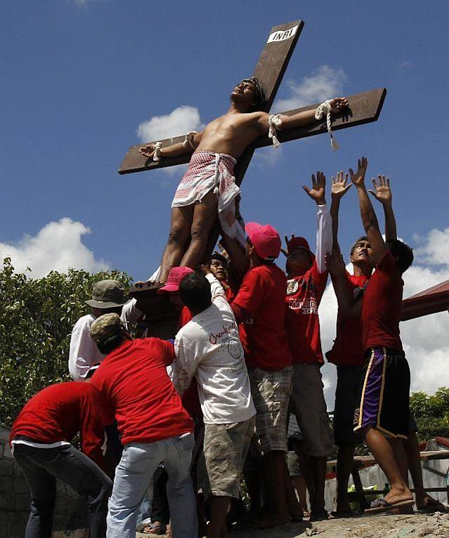 Rolly Pantajo, 58, who portrays Jesus Christ, is laid down after he was nailed on a wooden cross during a Good Friday crucifixion re-enactment in San Juan village, Pampanga province, north of Manila.