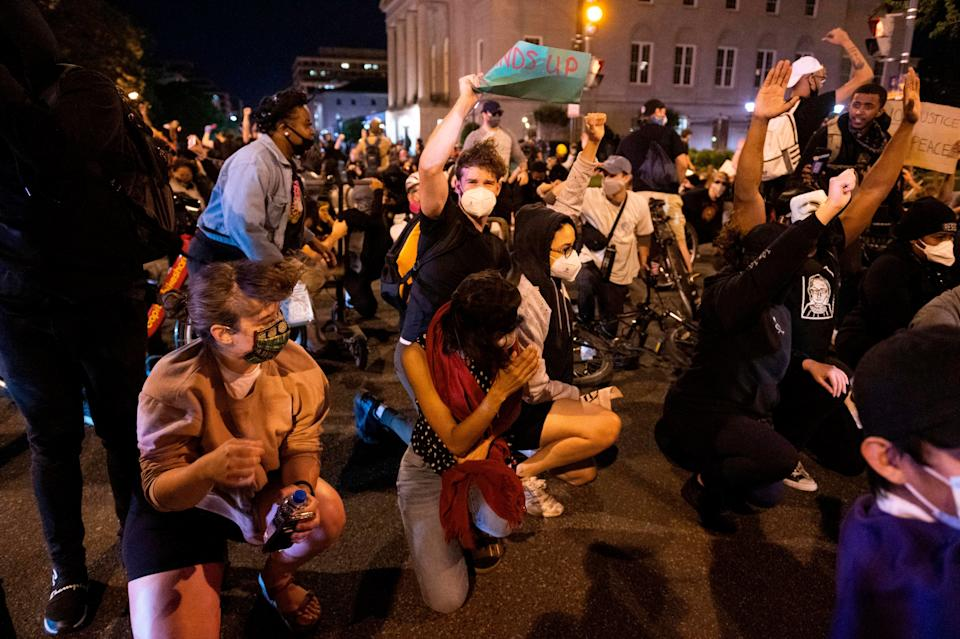 Demonstrators steady themselves as a military helicopter flies low over the crowd in Washington, D.C. during a protest over the death of George Floyd on June 1, 2020. (Photo: Roberto Schmidt/AFP via Getty Images)