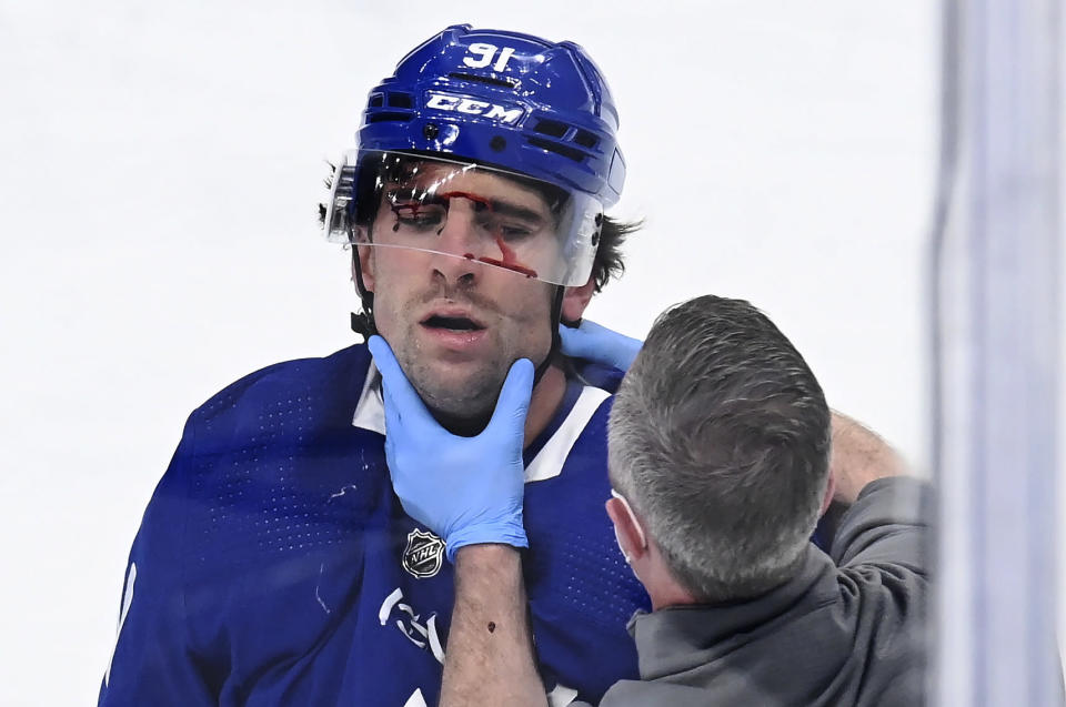 Toronto Maple Leafs forward John Tavares receives attention from a trainer after being injured during the first period against the Montreal Canadiens in Game 1 of an NHL hockey Stanley Cup first-round playoff series Thursday, May 20, 2021, in Toronto. (Frank Gunn/The Canadian Press via AP)
