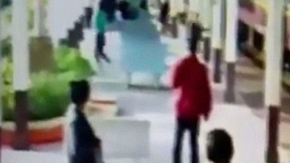 The moment the man, dressed in the green top can be seen running away. Source: CEN