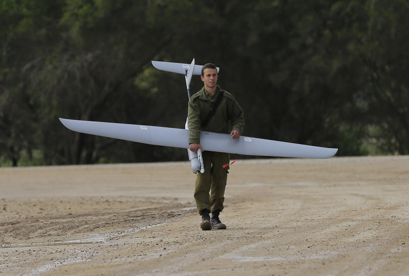 An Israeli soldier carries a drone near the Israel and Gaza border on Thursday, March 13, 2014. Gaza militants resumed rocket fire toward Israel on Thursday, striking the outskirts of two major cities a day after launching the largest barrage since an eight-day Israeli offensive in late 2012. Israel has responded with a series of airstrikes on militant targets. (AP Photo/Tsafrir Abayov)