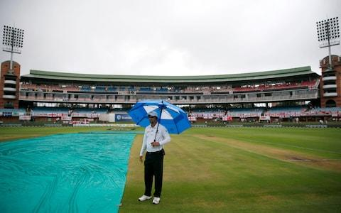 A match official stands under an umbrella next to the cover covering the pitch before the start of the match on the second day of the third Test cricket match between South Africa and England at the St George's Park Cricket Ground - Credit: GETTY IMAGES