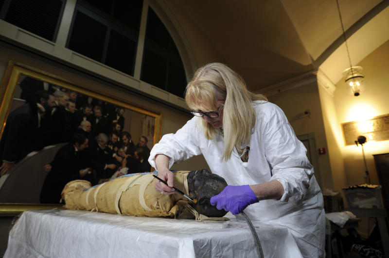 Mimi Leveque, a freelance conservator, cleans Padihershef, a 2,500-year-old Egyptian mummy at Mass General Hospital in Boston, Friday, June 7, 2013. Padihershef, who has made MGH his home since 1823, was a 40-year old stonecutter in the necropolis in Thebes, an ancient city on the west bank of the Nile. (AP Photo/Gretchen Ertl)