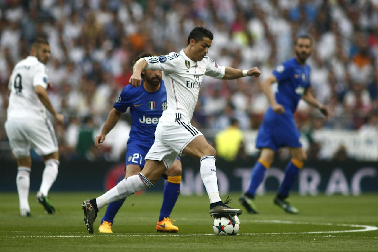 Real Madrid's Cristiano Ronaldo fights for the ball against Juventus' Andrea Pirlo during the Champions League second leg semifinal soccer match between Real Madrid and Juventus, at the Santiago Bernabeu stadium in Madrid, Wednesday, May 13, 2015. (AP Photo/Oscar del Pozo)