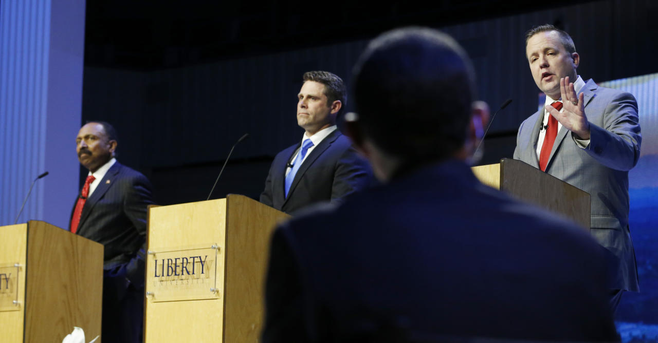 Republican primary senatorial candidate Corey Stewart, right, gestures as E. W. Jackson, left, Del. Nick Freitas, center, listen during a debate at Liberty University in Lynchburg, Va., Thursday, April 19, 2018. (AP Photo/Steve Helber)