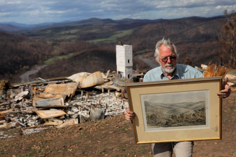 Donald Graham, 68, poses with a lithograph by Eugene von Guerard of the Buchan and Snowy Rivers, which Graham saved from a bushfire as he took shelter in his bunker with his wife Bron, as their home was destroyed by bushfires in Buchan, Victoria, Australia