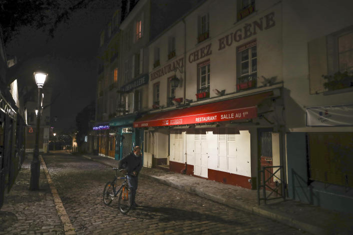 FILE - In this Dec. 15, 2020 file photo, a man pushes his bicycle along a row of closed restaurants in Montmartre, during the new imposed curfew in Paris. Trying to fend off the need for a third nationwide lockdown that would further dent Europe's second-largest economy and put more jobs in danger, France is instead opting for creeping curfews. (AP Photo/Michel Euler, File)