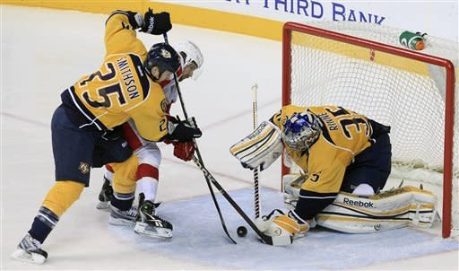 Nashville Predators goalie Pekka Rinne (35), of Finland, blocks a shot by Detroit Red Wings forward Darren Helm, center, as Predators center Jerred Smithson (25) also defends in the second period of an NHL hockey game Monday, Dec. 26, 2011, in Nashville, Tenn. (AP Photo/Mark Humphrey)