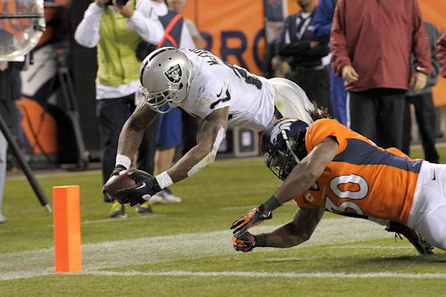 Oakland Raiders running back Darren McFadden (20) dives for the goal marker to score a touchdown against Denver Broncos strong safety David Bruton (30) in the fourth quarter of an NFL football game, Monday, Sept. 23, 2013, in Denver. (AP Photo/Jack Dempsey)