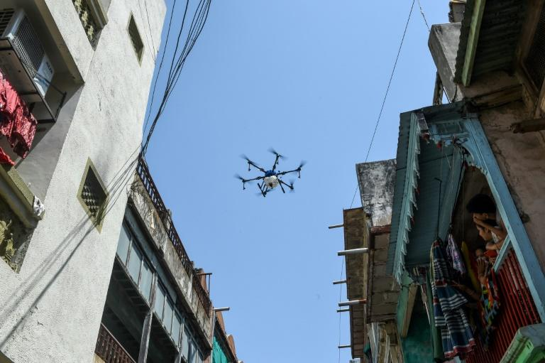 People in Ahmedabad in India - a new virus hotspot - watch from their balcony as a drone sprays disinfectant (AFP Photo/SAM PANTHAKY)