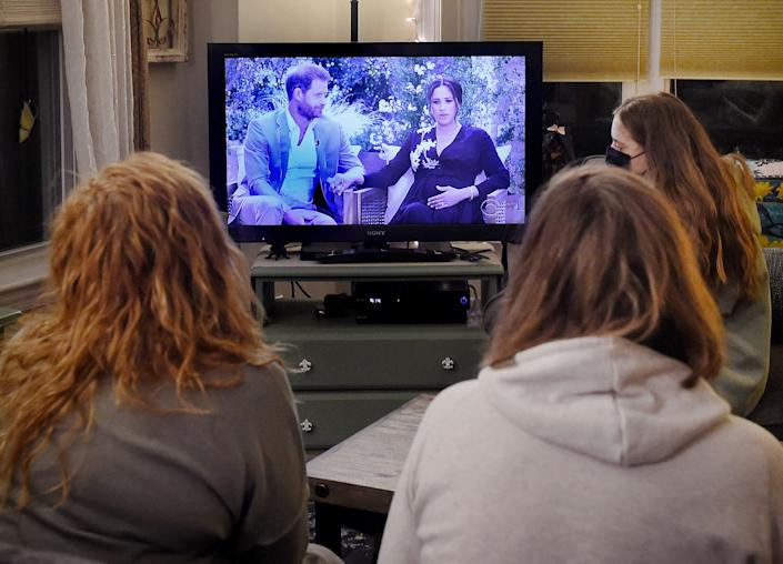 This photo illustration shows people wearing face masks, watch a televised conversation between Britain's Prince Harry with his wife Meghan Markle and US host Oprah Winfrey, in Arlington, Virginia March 7, 2021. - Britain's royal family on Sunday braced for further revelations from Prince Harry and his American wife, Meghan, as a week of transatlantic claim and counter-claim reaches a climax with the broadcast of their interview with Oprah Winfrey. The two-hour interview with the US TV queen is the biggest royal tell-all since Harry's mother princess Diana detailed her crumbling marriage to his father Prince Charles in 1995. (Photo by OLIVIER DOULIERY / AFP) (Photo by OLIVIER DOULIERY/AFP via Getty Images)