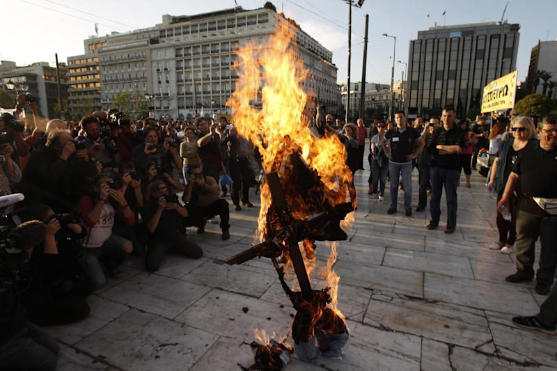 A protester burns an effigy depicting a Greek worker during a protest in front of the Parliament in Athens, Sunday April 28, 2013. A few hundred public servants protested peacefully outside the Greek Parliament as lawmakers voted on new austerity bill.(AP Photo/Kostas Tsironis)
