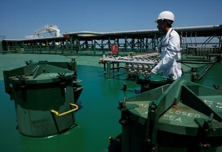 A crew member walks past cargo tank openings on the deck of Hin Leong's Pu Tuo Shan VLCC supertanker in the waters off Jurong Island in Singapore