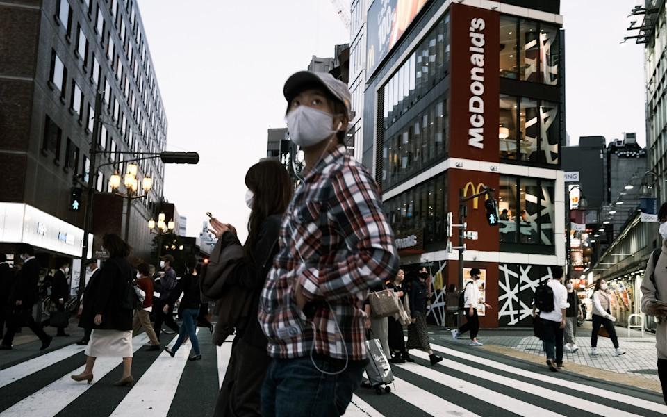 Pedestrians wearing protective masks cross a road in the Shinjuku district of Tokyo, Japan - Soichiro Koriyama