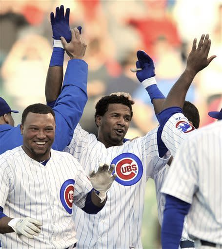 Chicago Cubs' Julio Borbon center, celebrates with teammates after hitting a walkoff-single to defeat the Cincinnati Reds 6-5 in fourteen innings of an MLB baseball game in Chicago, Thursday, June 13, 2013. (AP Photo/Paul Beaty)