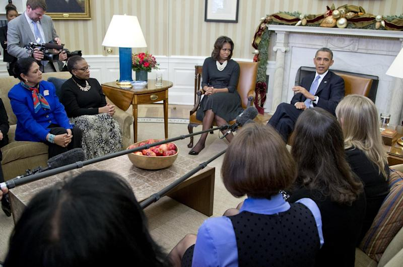 President Barack Obama gestures as he speaks to the media as he and first lady Michelle Obama meet with a group of mothers in the Oval Office of the White House in Washington, Wednesday, Dec. 18, 2013, to discuss how health care reform could benefit their families. (AP Photo/Carolyn Kaster)