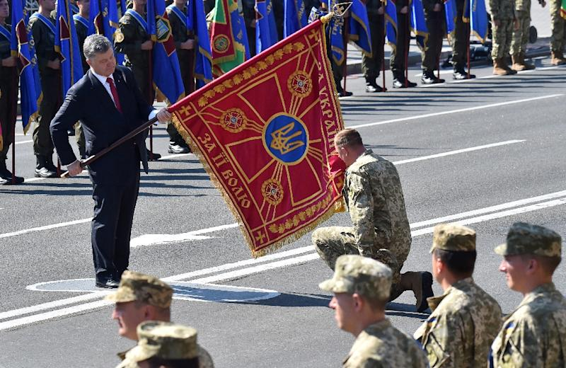 Ukrainian President Petro Poroshenko (left) holds a flag during an Independence Day military parade in Kiev on August 24, 2015 (AFP Photo/Sergei Supinsky)