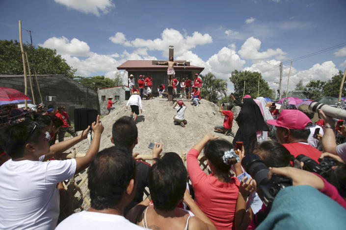 Tourists take pictures of a Filipino penitent who is nailed to the cross during Good Friday rituals on March 29, 2013 at San Juan, Pampanga province, northern Philippines. Several Filipino devotees had themselves nailed to crosses Friday to remember Jesus Christ's suffering and death, an annual rite rejected by church leaders in this predominantly Roman Catholic country. (AP Photo/Aaron Favila)